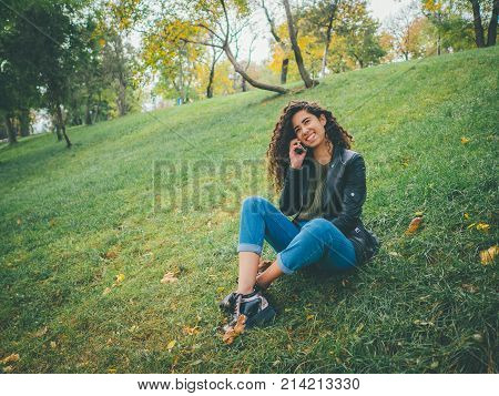 Beautiful young curly haired latin girl using her cell phone, outdoor. Portrait of relaxed young hispanic lady in green park, talking on phone.