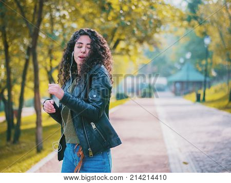 Happy african young woman with curly hair listening to music on earphones. Hispanic hipster girl dancing to rhythm and singing along melody in the park.