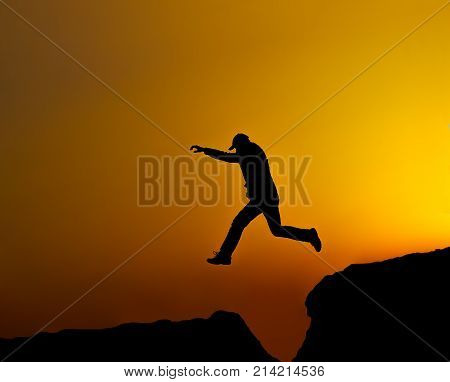 Silouette, running and jumping man at sunset