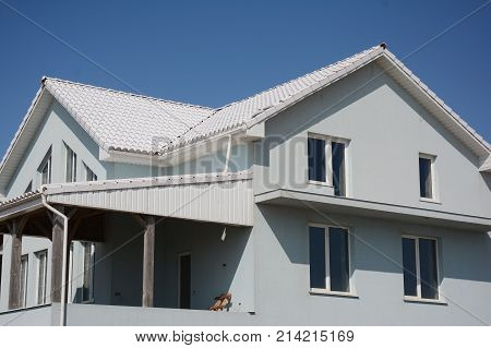 House with white tiled roof for energy saving. Roofing construction. White Roof Bring Cool Savings and can reduce air conditioning costs by up to 20 percent.
