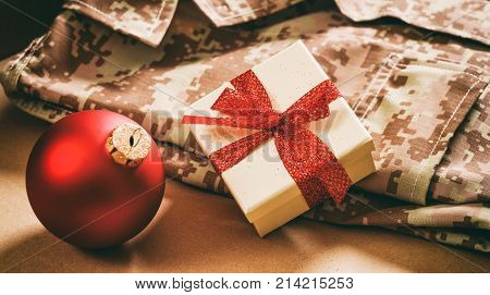 Christmas in the army concept. Christmas ball and gift box on an American soldier uniform