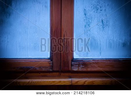 Old window in a wooden frame with a frost pattern on the window glass (in the evening light)