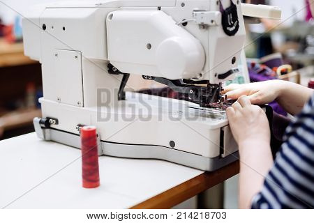 Woman working on a sewing machine in textile industry
