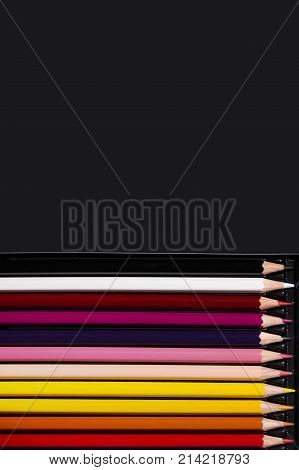 Multicolour pencils on black background. Art and creativity concept. Copy space