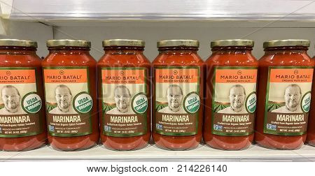 Boston October 29 2017: Jars of Mario Batali marinara sauce stand on a shelf in a high end grocery store.