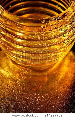Golden texture with water drops. Thirst and its quenching. Drops of honey on the glass