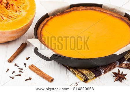 Freshly baked pumpkin pie in a cast iron pan cools on the table