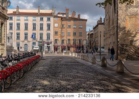 Lyon France -- November 6 2017 -- A row of bicycles is parked by a cobblestone street leading to shops and restaurants in the old city section of Lyon. Editorial Use Only.