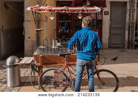 Lyon France -- November 6 2017 -- A cyclist stops by a food cart outside a restaurant in Lyon. Editorial Use Only.