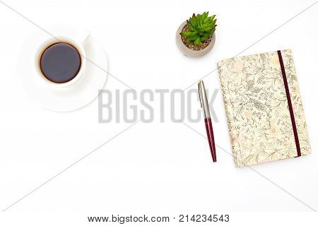 A cup of coffee and a notebook on a white background. Mockup