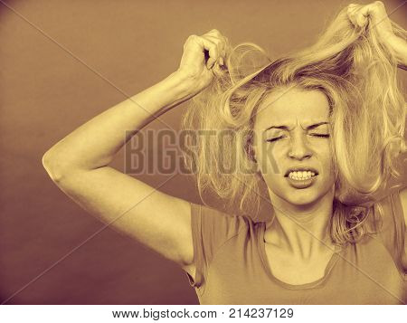 Haircare health problem concept. Frustrated depressed woman holding and pulling out her damaged blonde hair with closed eyes. Sepia