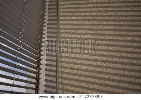 Blinds and shadows of blinds on an office wall