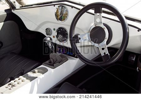 Part of old vintage white car inside with driving wheel