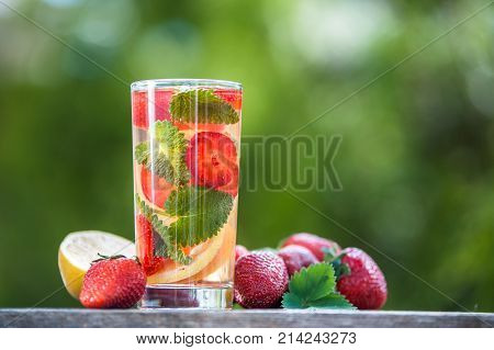A glass of detox water. Strawberry lemon and mint with cool clean water backdrop of a green garden. Detox diet Cookery sports proper nutrition sports nutrition body cleansing