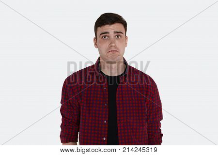 I don't know. Picture of funny young male raising eyebrows and screwing up lips having clueless confused facial expression. Brunette man dressed in casual shirt staring at camera in confusion