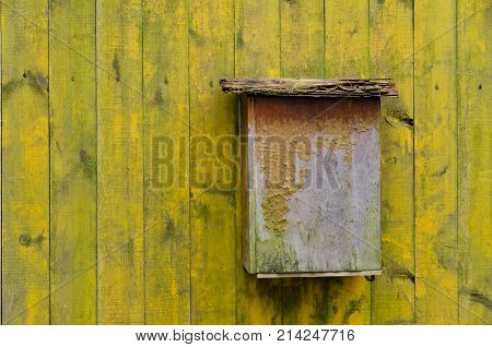 The old plywood mailbox is on a yellow fence. The paint on the mailbox and the fence peeled off. Background. Texture.