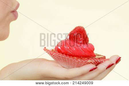 Sweets junk food sugar temptation on diet concept. Woman holding sweet delicious cupcake sending air kisses to dessert.