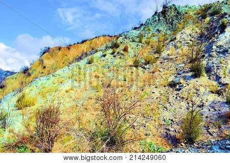 Desolate landscape with burnt chaparral shrubs caused from a wildfire on a barren hillside with a greenish blue tint which represents minerals in the rocks and soil taken in Cajon, CA
