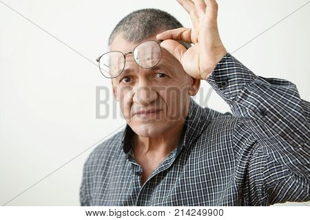 Head and shoulders of handsome long sighted senior man of Caucasian appearance wearing spectacles to see close objects clearly posing at white studio wall with copy space for yout information