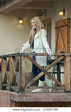 Outdoor Portrait of Beautiful Blond Young Woman on Balcony