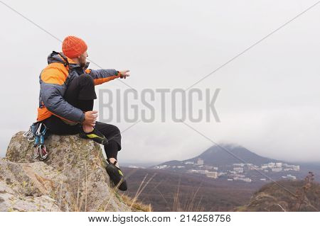 Hipster - a climber in a down jacket and a knitted hat sits on top of a rock and points with his hand to the side where you can see the autumnal ponamram of neighboring mountains and cities in cloudy weather.