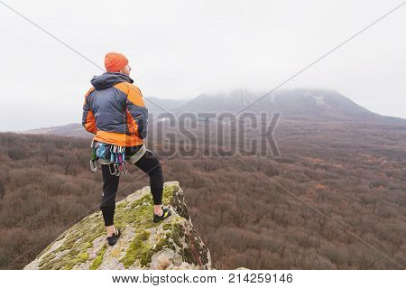 Hipster - a rock climber in a down jacket and a knitted cap is standing and meditating meditating looking at the autumnal ponamramu of neighboring mountains and cities in cloudy weather.