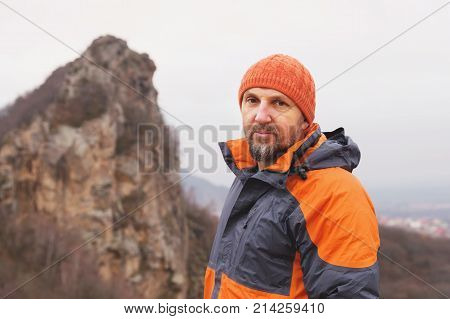 Portrait of a hipster-climber aged and with a beard against a sharp mountain in the northern Caucasus. Autumn portrait of a climber in a down jacket and a knitted cap. The concept of a healthy lifestyle and outdoor activities