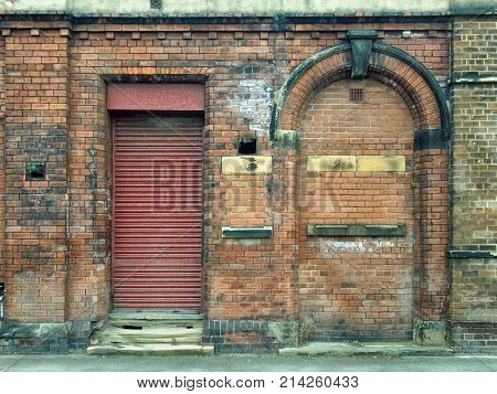 old abandoned derelict industrial premises with bricked up arched doorway and closed red metal shutters
