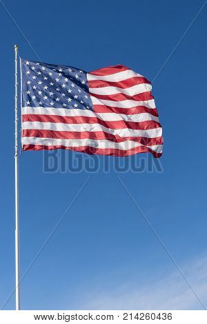 A red white and blue American flag with stars and stripes unfurled in the wind. Photographed against a deep blue sky with cirrus clouds.