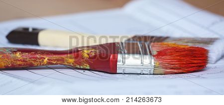 Two paint brushes lying on paper