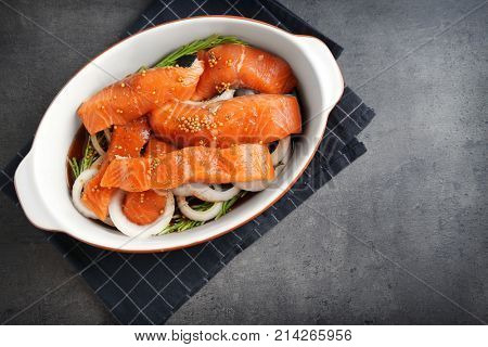 Casserole dish with marinated slices of salmon fillet on table
