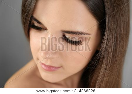 Beautiful young woman with eyelash extension on light background