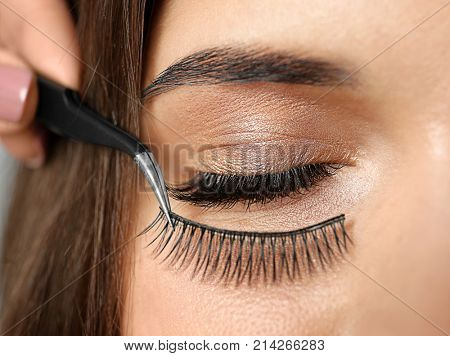 Young woman undergoing eyelash extension procedure, closeup