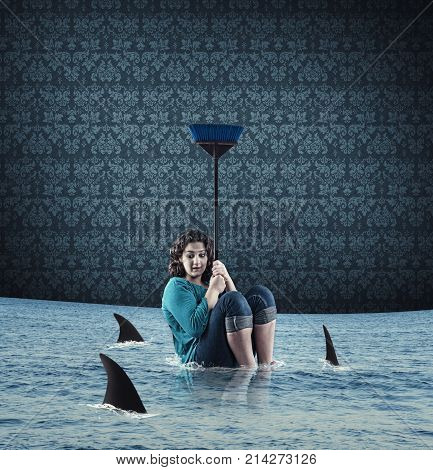 Scared woman protect herself from sharks with a broom in her flooded house.