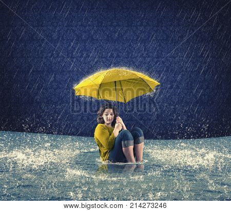 Scared woman holding an umbrella while it raining in the house and the floods came inside.