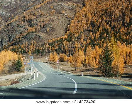 View from inside car window to the road and autumn mountain landscape. Asphalt road in perspective. View of the road layout of car windshield view of the sky. Autumn forest.