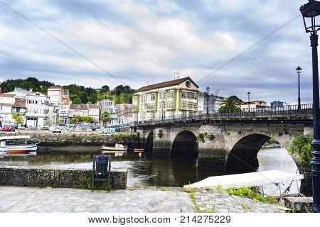 Roman Bridge Over The Ria De Betanzos With A Strong Current And In The Middle Of A Town In Galicia,