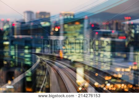Motion blurred train curved with blurred bokeh city light double exposure