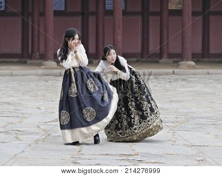 seoul south korea - 10th november 2017: young korean girls in traditional hanbok dresses at gyeongbokkung palace. gyeongbokgung palace is the most beautiful and the largest of all five palaces.