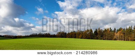 Panoramic view of colorful autumnal landscape with green meadow trees and blue sky with clouds - Czech Republic
