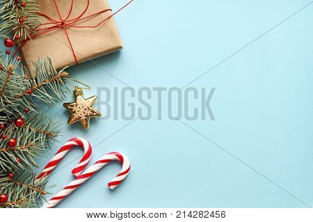 Christmas background. Composition with Christmas gift box fir tree branch candy canes and decorations on blue background. Top view with copy space.
