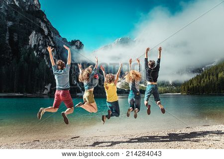 Group of friends having a walk on a mountain lake - Young people exploring the nature