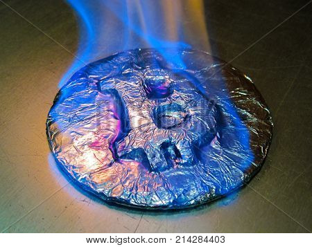 Bitcoin metal silver coin is burning with blue flame. It means hot price or value and high exchange rate of crypto currency on market. It also means crisis and fall to lose investments due to financial risk