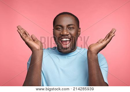 Happy Attractive African American Man Laughs At Good Joke, Claps Hands, Being Very Emotional And Ove