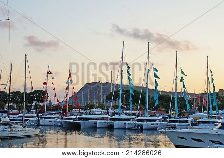 The bay with yachts is surrounded by low hills. Sunset over the bay. Harbor with yachts in Barcelona. Marina for yachts in the Mediterranean.