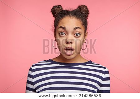 Isolated Portrait Of Shocked African Dark Skinned Female Has Two Buns, Dressed Casually, Astonished