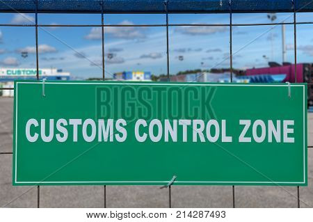 Green sign customs control zone on the fence of the logistic customs terminal.