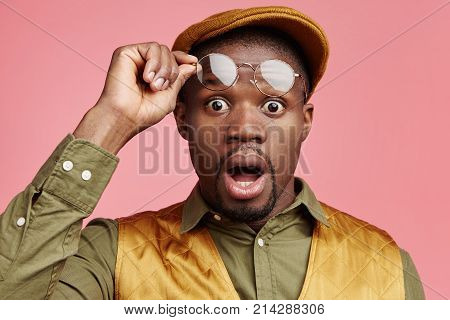 Stupefied Black Male Model Takes Off Glasses, Stares At Camera, Has Greatly Surprised Look, Realizes