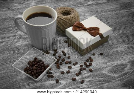hank of threads, gift box, coffee beans and cup of cofee on gray wood background