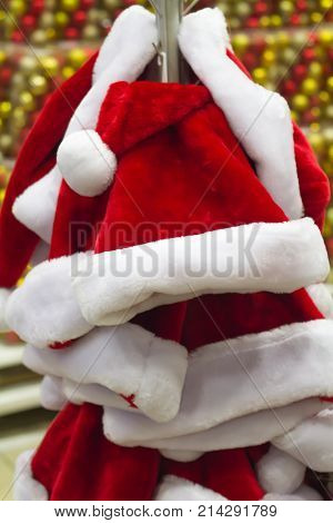 Santa Claus hat many in supermarket shop for sale hanging on the rack close-up